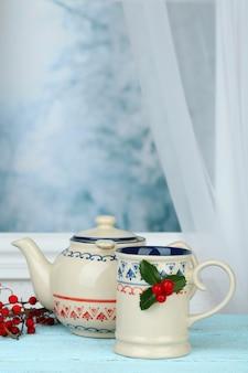 Composição de natal com xícara e bule de bebida, na mesa de madeira