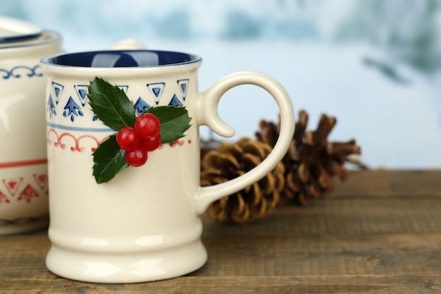 Composição de natal com xícara e bule de bebida quente, na mesa de madeira