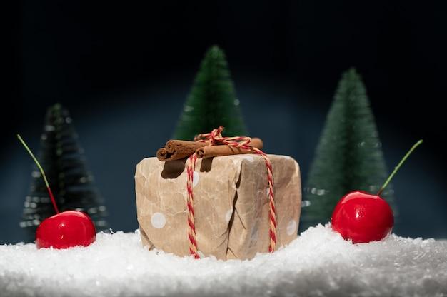 Composição de natal composta por um presente deitado na neve e maçãs vermelhas