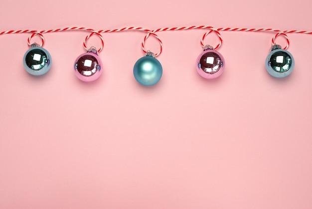 Composição de natal, cores da moda. banner de guirlanda de natal brilhante com bolas rosa e azul celeste sobre fundo rosa. natal, inverno, conceito de ano novo. vista frontal