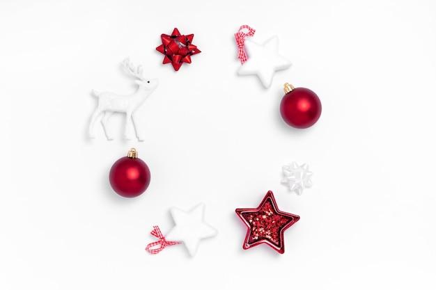 Composição de natal. coroa de bolas vermelhas, estrelas brancas, veados em fundo de papel branco.