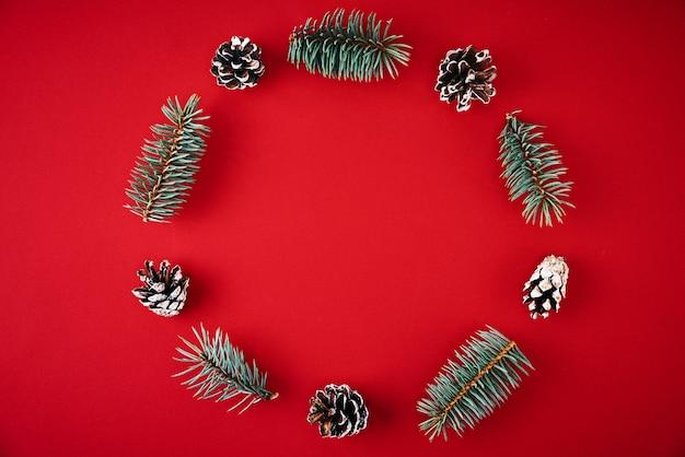 Composição de natal. coroa de flores feita de galhos de árvores de abeto e pinhas festivas em fundo vermelho, vista superior