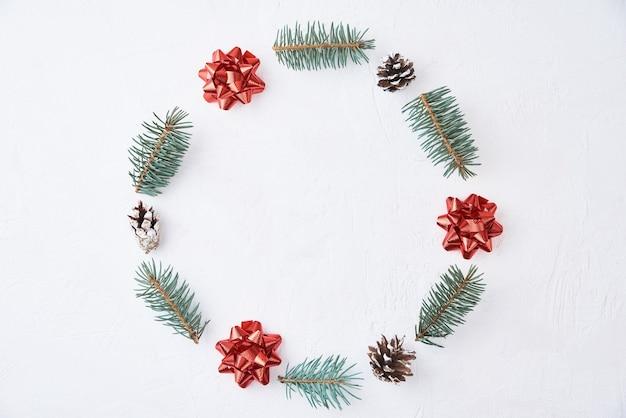 Composição de natal. coroa de flores feita de galhos de pinheiros e pinhas festivas em fundo branco, vista superior