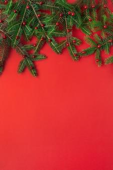 Composição de natal de ano novo. galhos de pinheiro com bagas vermelhas no vermelho