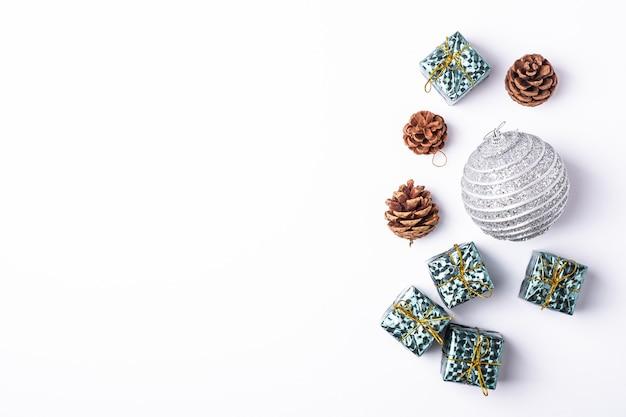 Composição de natal de ano novo. presentes, cones de árvore do abeto, decorações de bola de prata sobre fundo branco. conceito de férias de inverno. camada plana, vista superior, espaço de cópia