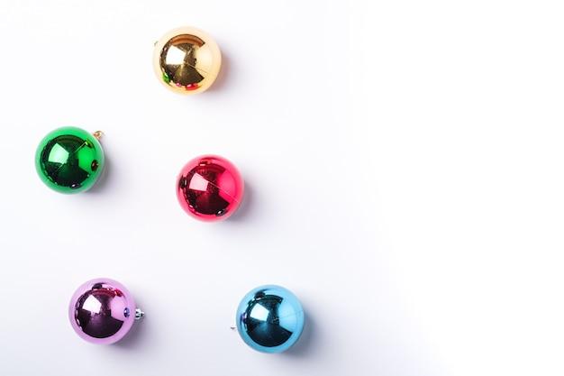 Composição de natal de ano novo. presentes, decorações de bola coloridas em fundo branco. conceito de férias de inverno. camada plana, vista superior, espaço de cópia
