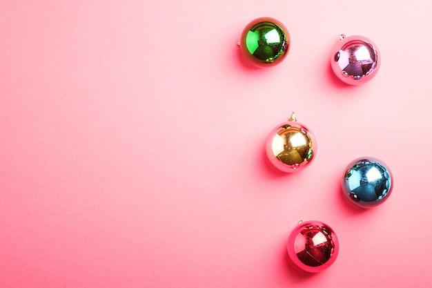 Composição de natal de ano novo. presentes, decorações de bola coloridas em fundo rosa. conceito de férias de inverno. camada plana, vista superior, espaço de cópia