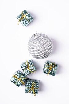 Composição de natal de ano novo. presentes, decorações de bola de prata sobre fundo branco. conceito de férias de inverno. camada plana, vista superior