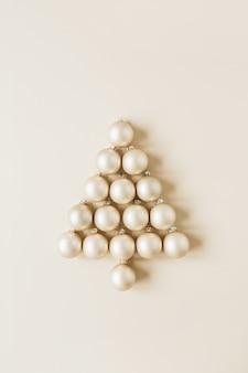Composição de natal de ano novo. símbolo da árvore de natal feito de enfeites de natal dourados em bege
