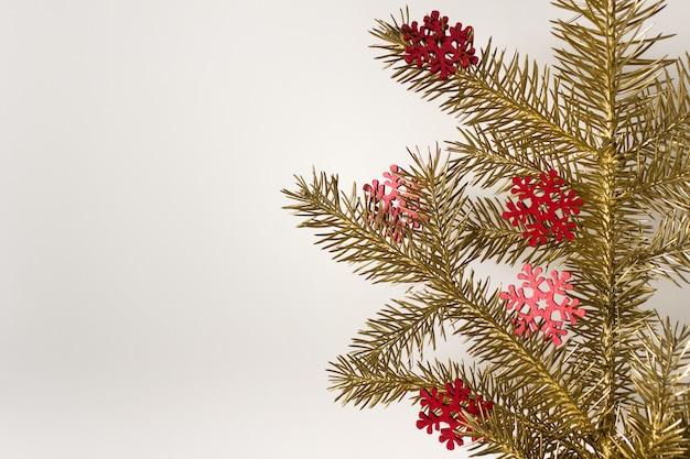Composição de natal de cartão comemorativo com árvore perene dourada e flocos de neve de madeira vermelhos