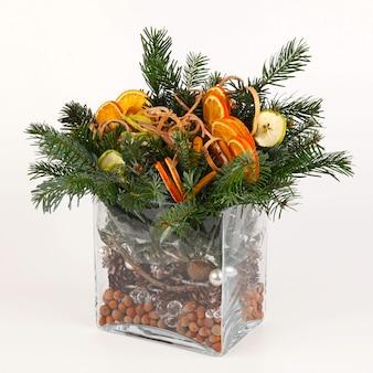 Composição de natal de ramos de pinheiro, fatias de maçã e laranja, pinhas, casca e avelãs. em vaso retangular de vidro liso. em fundo branco