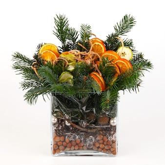 Composição de natal de ramos de pinheiro, fatias de maçã e laranja, pinhas, casca e avelãs. em vaso retangular de vidro liso. vista frontal. em fundo branco
