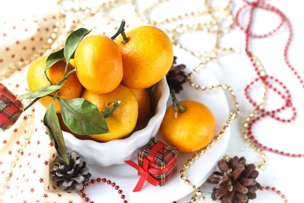 Composição de natal de tangerina em uma tigela branca, cone, guirlanda e velas em um fundo branco