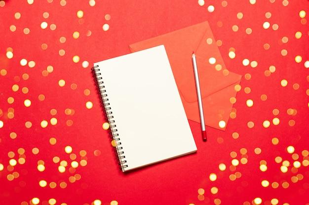 Composição de natal de um papel vazio com um lápis para escrever uma lista de desejos de natal. conceito de férias.