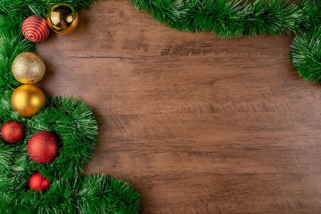 Composição de natal. decorações com bolas de natal vermelhas e douradas em fundo de madeira. vista superior, copie o espaço.