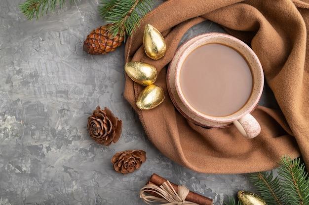 Composição de natal. decorações, cones, canela, ramos de abeto e abeto, xícara de café, lenço de lã em concreto cinza. postura plana.