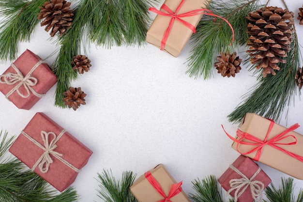Composição de natal. decorações de natal brancas, galhos de árvore do abeto com caixas de presente de brinquedos em fundo branco. camada plana, vista superior, cópia espaço, cartão comemorativo