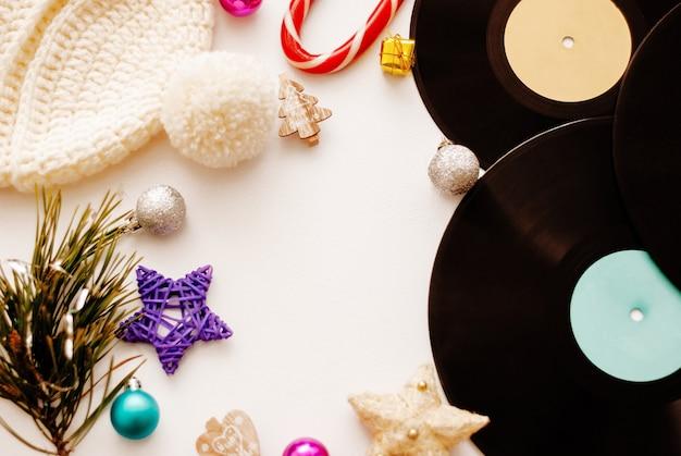 Composição de natal. decorações de natal, chapéu e vinil em fundo branco. vista plana leiga