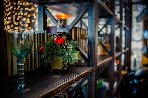 Composição de natal. decorações de natal em uma estante de livros, decoração de madeira, enfeites, guirlanda.