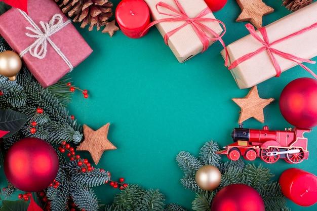 Composição de natal. decorações de natal verde, galhos de árvore do abeto com caixas de presente de brinquedos sobre fundo verde. camada plana, vista superior, espaço de cópia.
