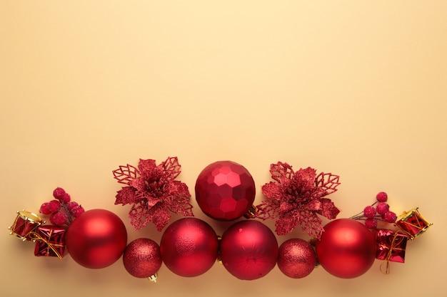 Composição de natal. decorações de natal vermelhas e douradas sobre fundo bege. camada plana, vista superior, espaço de cópia