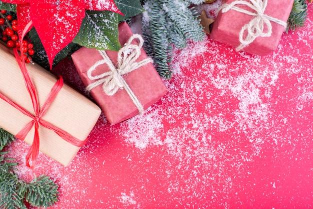 Composição de natal. decorações de natal vermelhas, galhos de árvore do abeto com caixas de presente de brinquedos em fundo vermelho. camada plana, vista superior, espaço de cópia.
