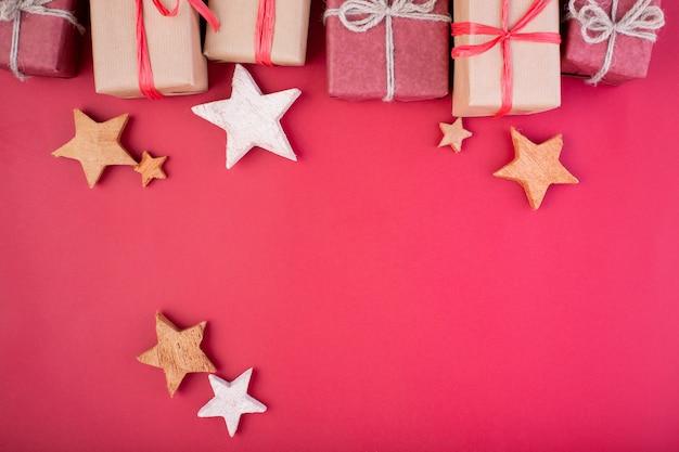 Composição de natal. decorações de natal vermelho, estrelas e caixas de presente em fundo vermelho