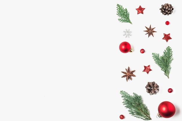 Composição de natal. decorações vermelhas, galhos de árvores de abeto, pinhas em fundo branco. natal, inverno, conceito de ano novo. camada plana, vista superior com espaço de cópia
