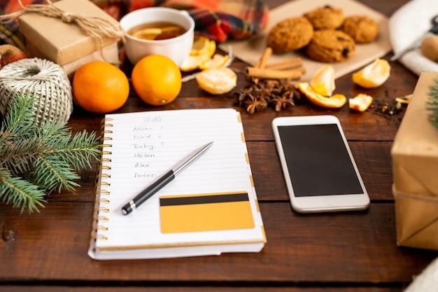 Composição de natal do smartphone, página do bloco de notas com lista, caneta e cartão de crédito entre coisas festivas na mesa de madeira