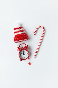 Composição de natal, doces de cana, pequeno relógio analógico, chapéu listrado, estrela, dispostos em forma de coração em background.media branco, cartão de felicitações.