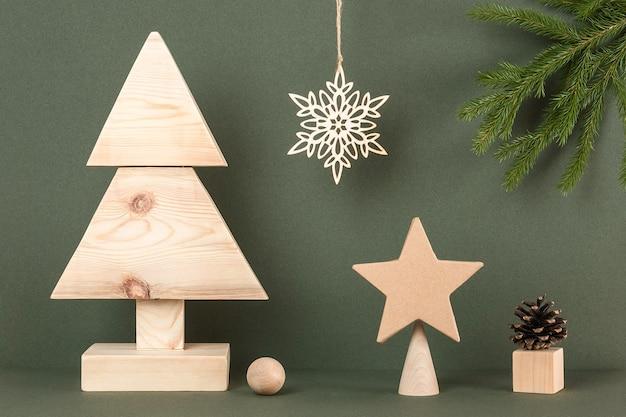 Composição de natal e ano novo. árvore de natal de madeira caseira e decoração do feriado sobre fundo verde. férias do conceito criativo. vista frontal.