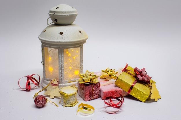 Composição de natal e ano novo. lanterna brilhante festiva com decorações, presentes e laços brilhantes em um fundo branco.