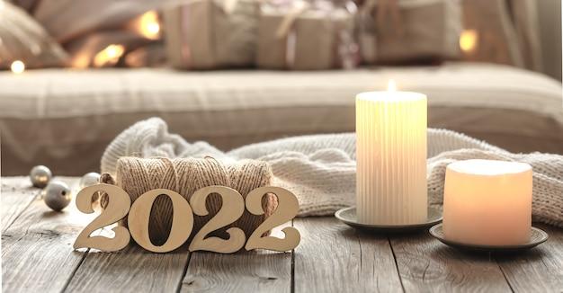 Composição de natal em casa com números decorativos de madeira 2022, velas e detalhes de decoração em um fundo interior de quarto desfocado.