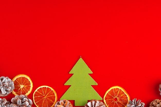 Composição de natal em fundo vermelho com pinhas