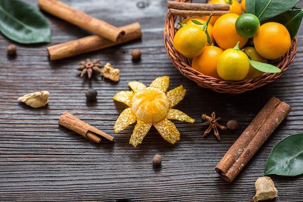 Composição de natal em madeira velha. natureza morta com calamondinas na cesta, paus de canela, estrela de anis, cardamomo, gengibre. vista lateral