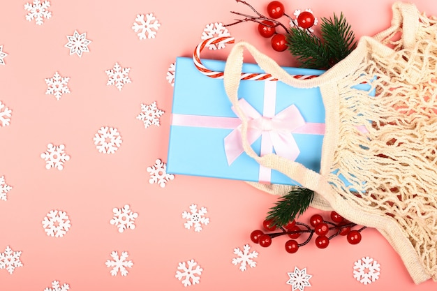 Composição de natal em um fundo rosa. desperdício zero. saco reutilizável ecológico com presentes de ano novo. conceito criativo. estilo simples, vista superior.