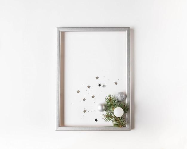 Composição de natal em uma moldura de prata com um ramo de abeto e bolas de natal de prata e confetes