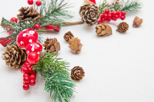 Composição de natal. galho de árvore do abeto, decorações vermelhas sobre branco
