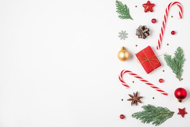Composição de natal. galhos de árvores de abeto, caixas de presente, decorações, doces, pinhas em fundo branco. natal, inverno, conceito de ano novo. postura plana. vista de cima com espaço de cópia