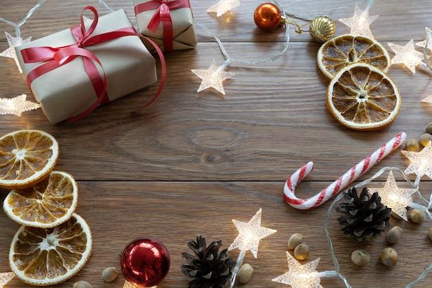 Composição de natal. layout de ano novo em um fundo escuro de madeira. cones, brinquedos, presentes, guirlandas.