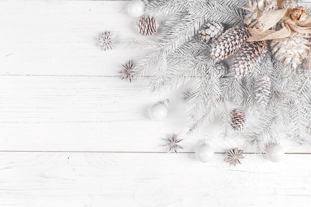 Composição de natal. moldura feita de ramos de abeto em fundo branco de madeira