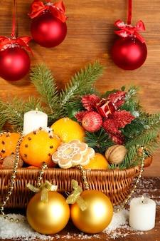 Composição de natal numa cesta com laranjas e pinheiros, em fundo de madeira.