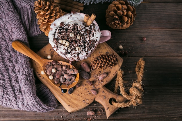 Composição de natal ou ano novo com chocolate quente ou bebida de cacau com creme chantilly servida com chocolate picado e grãos de cacau na placa de madeira rústica. vista do topo