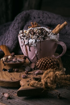 Composição de natal ou ano novo com chocolate quente ou bebida de cacau com creme chantilly servida com chocolate picado e grãos de cacau na placa de madeira rústica.