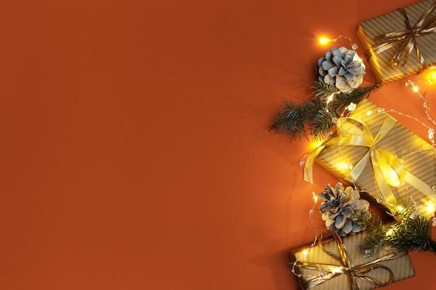 Composição de natal ou ano novo com luzes e presentes dourados de decorações de natal