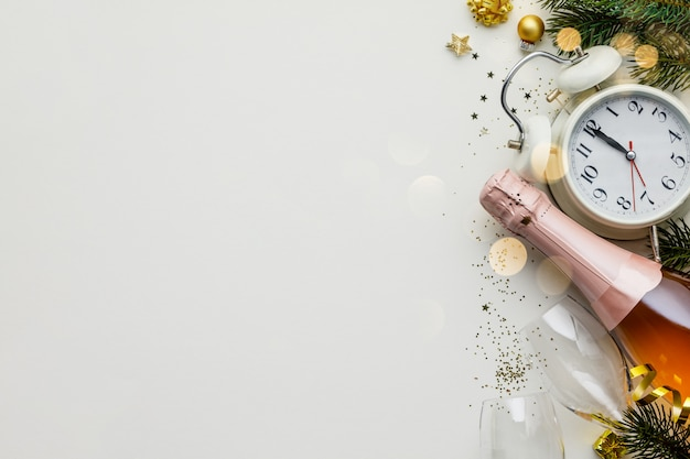 Composição de natal ou ano novo em fundo branco com despertador retrô, garrafa de champanhe, copos e decorações de natal