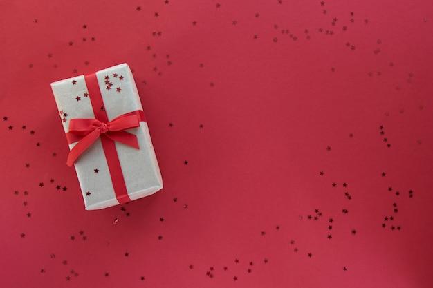 Composição de natal ou dia dos namorados com espaço de cópia. giftbox com fita vermelha e decorações de confetes em fundo colorido de papel pastel.
