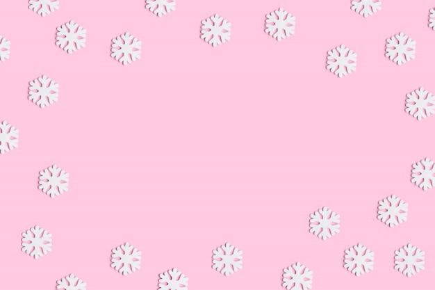 Composição de natal ou inverno de flocos de neve em fundo rosa pastel.