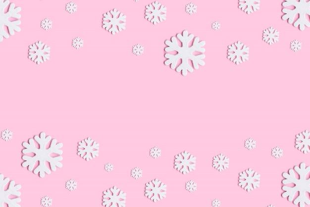 Composição de natal ou inverno. teste padrão feito de flocos de neve no fundo rosa pastel.