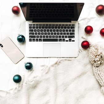 Composição de natal para o ano novo vista plana leiga de cima laptop e celular deitado na cama branca com cobertor branco decorado com bolas vermelhas e azuis de natal e chapéu de malha de inverno